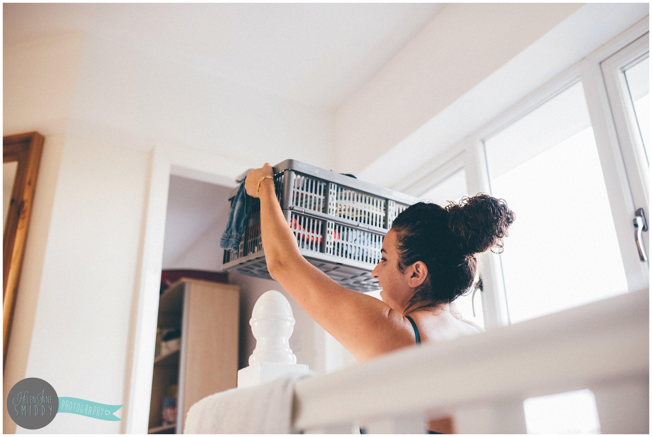 Nina carrying washing upstairs whilst starting her day.