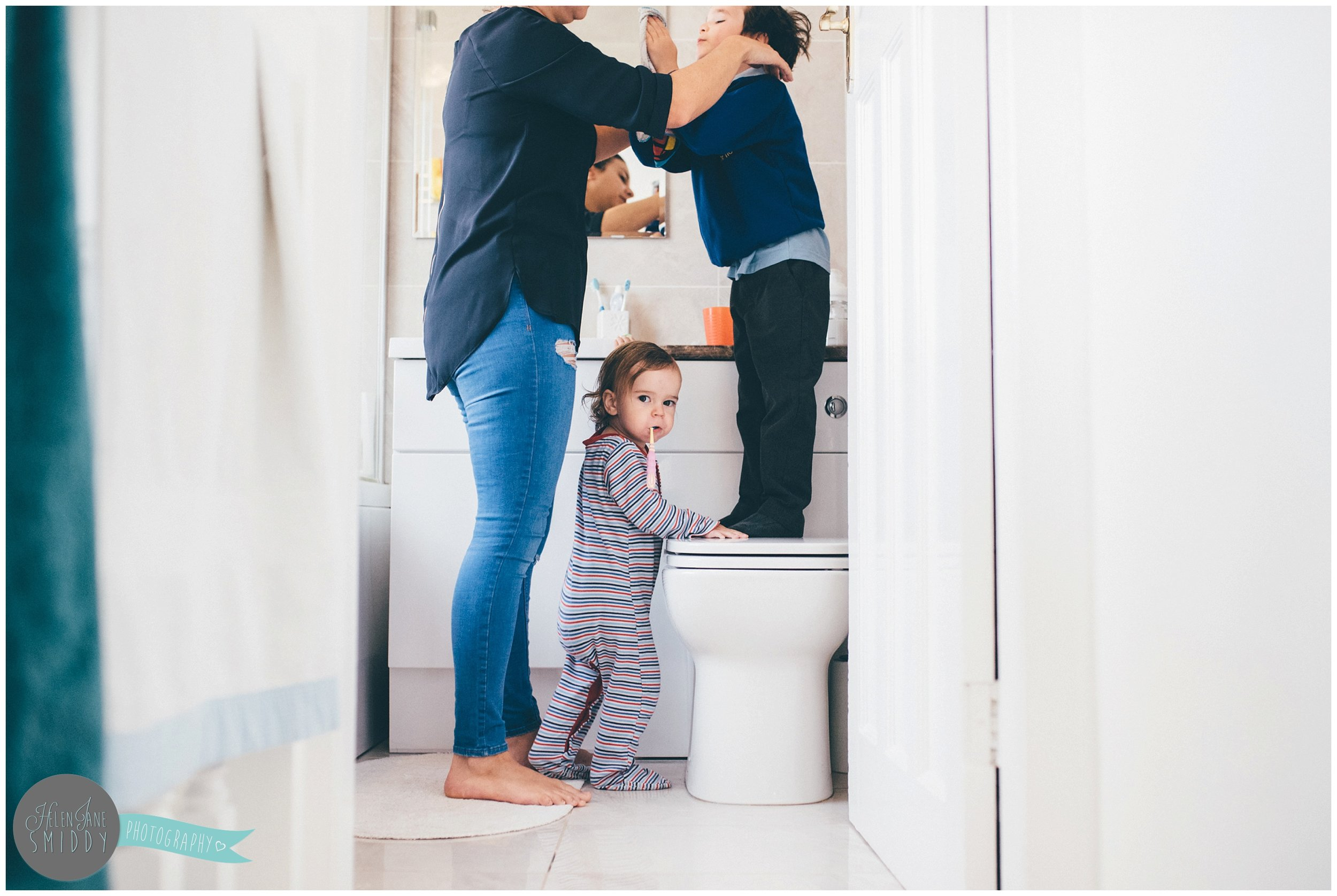 A mother brushes her sons hair whilst her daughter brushed her teeth. alongside them.