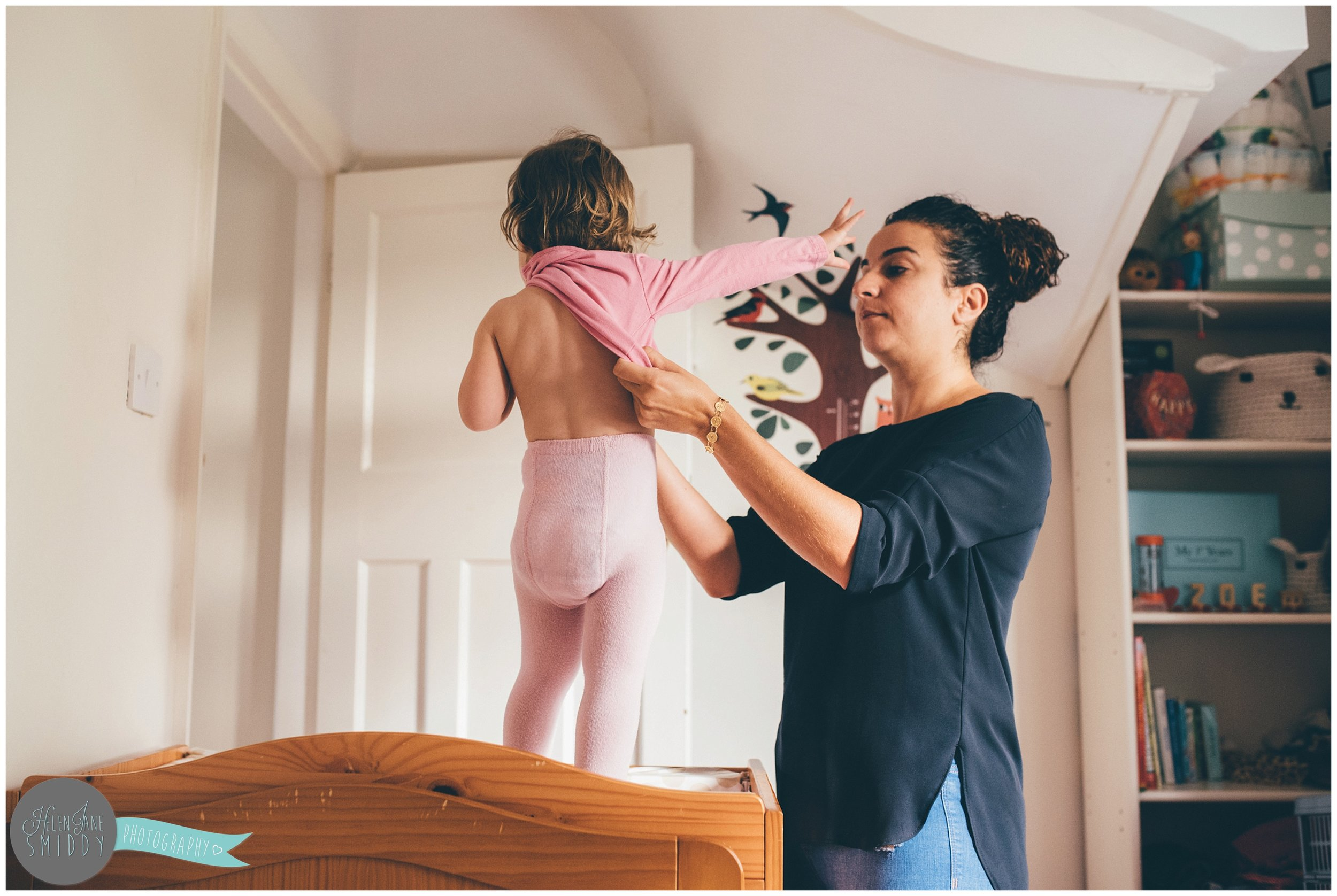 A mummy dresses her daughter in a pretty pink tshirt.
