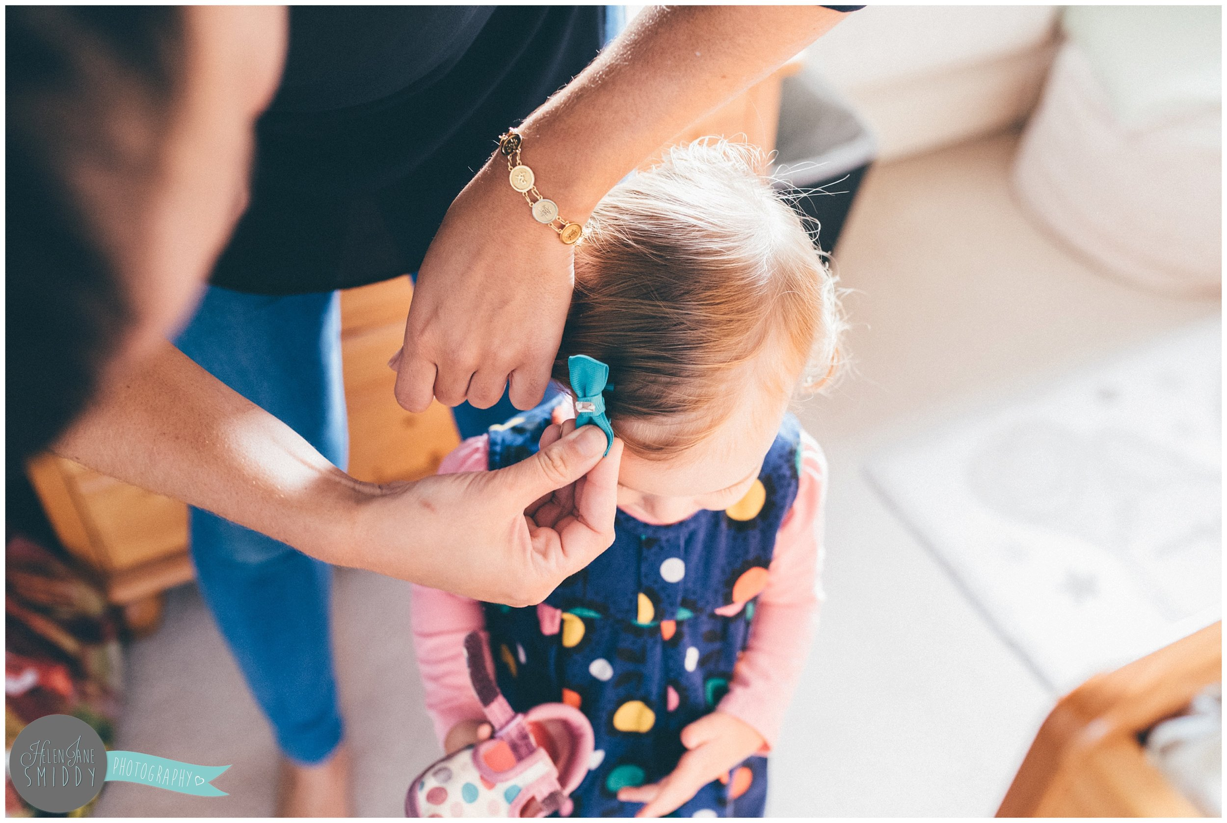 Little girl gets a bow put in her hair by her Mummy.