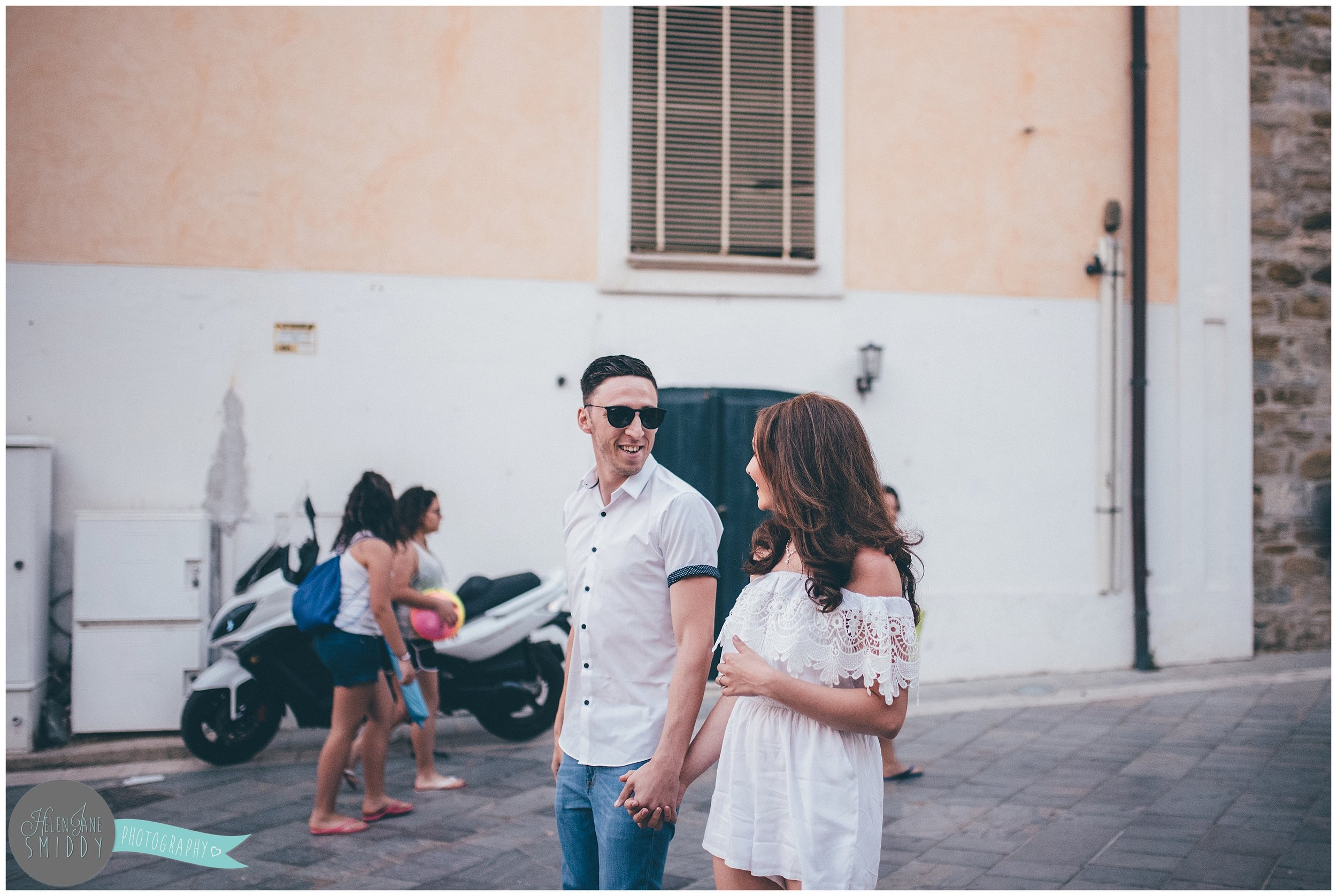 The engaged couple smile at each-other whilst walking through the Italian streets.