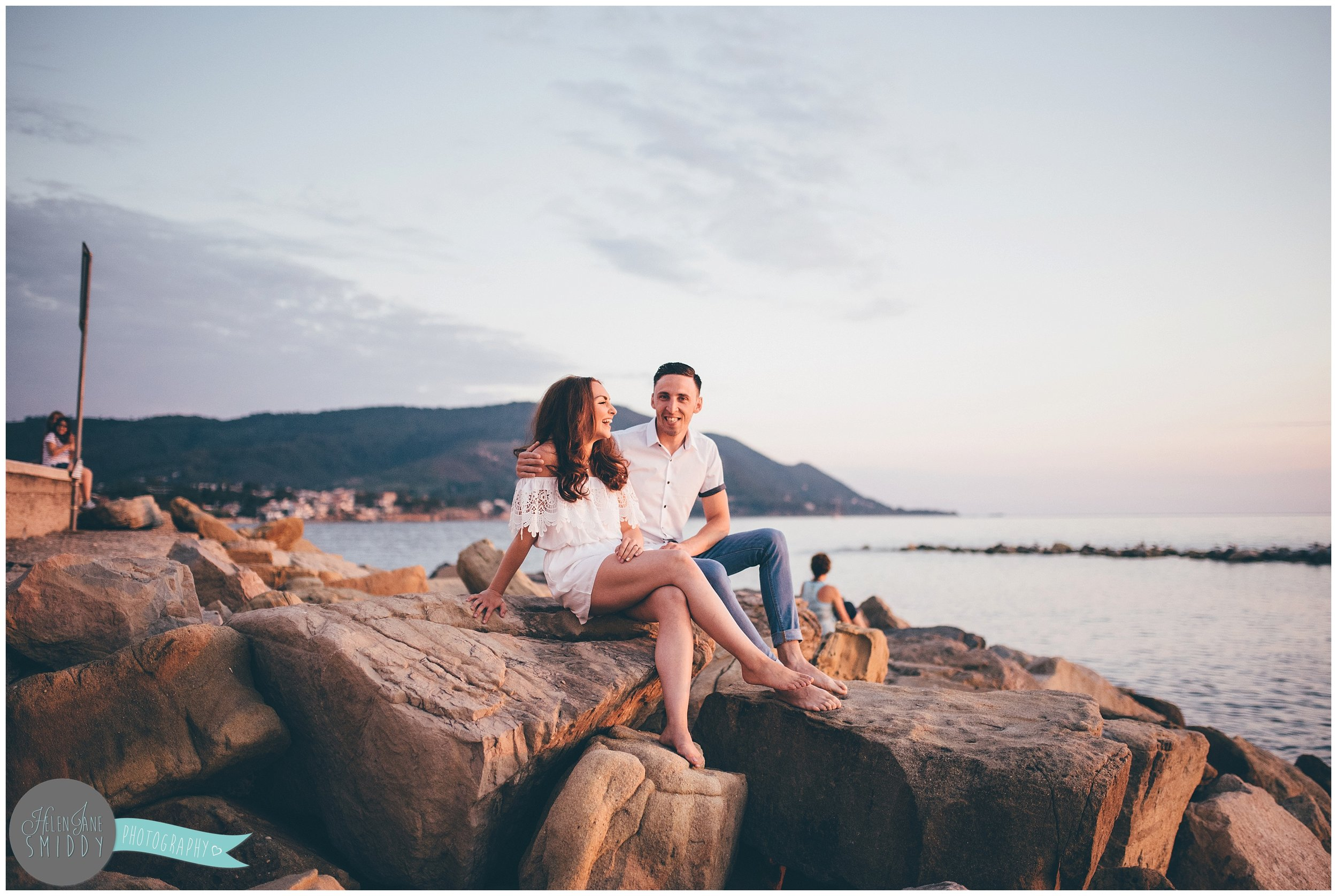 The young couple sit on the rocks on the beach during their Engagement photoshoot in Santa Maria Di Castellabate, Italy.