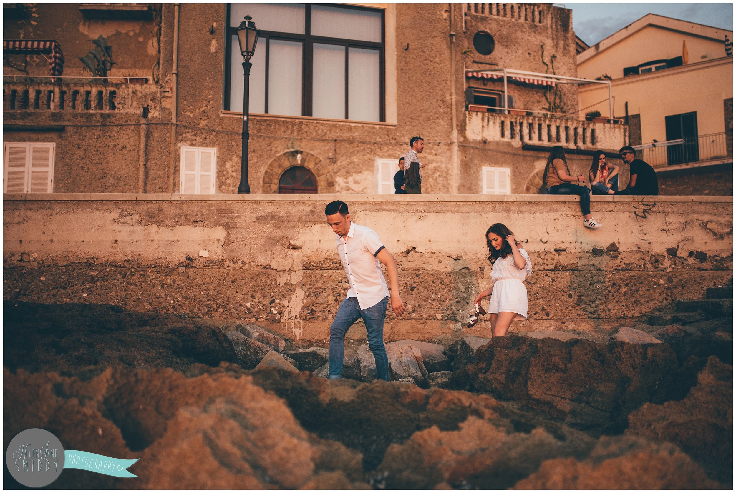 The young couple make their way through the rocks on the beach during their Engagement photoshoot in Santa Maria Di Castellabate, Italy.