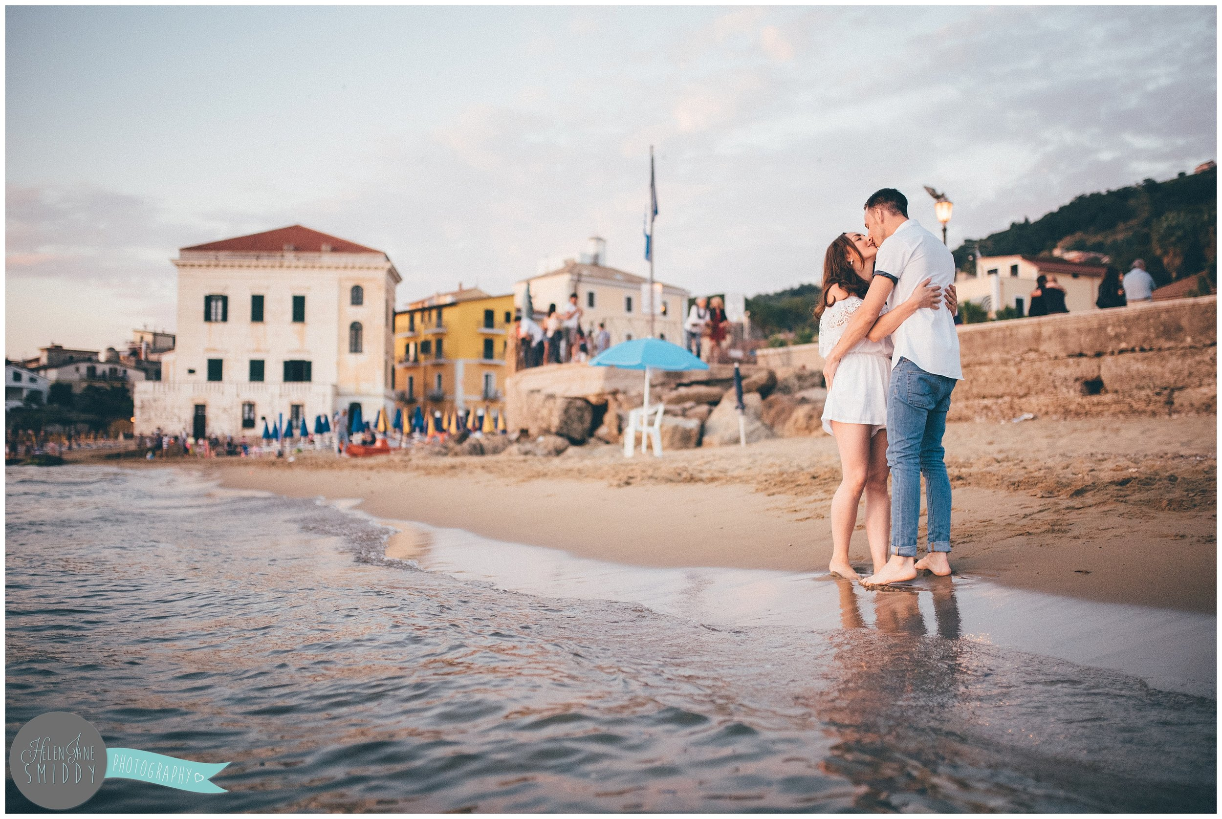 The couple stand in the water kissing, with Santa Maria di Castellabate in the background.