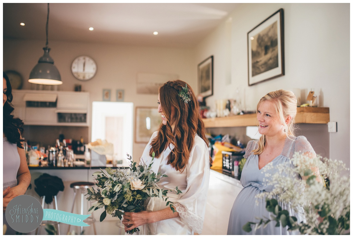 The bride laughs with her bridesmaids at Barn Drift in Norfolk.