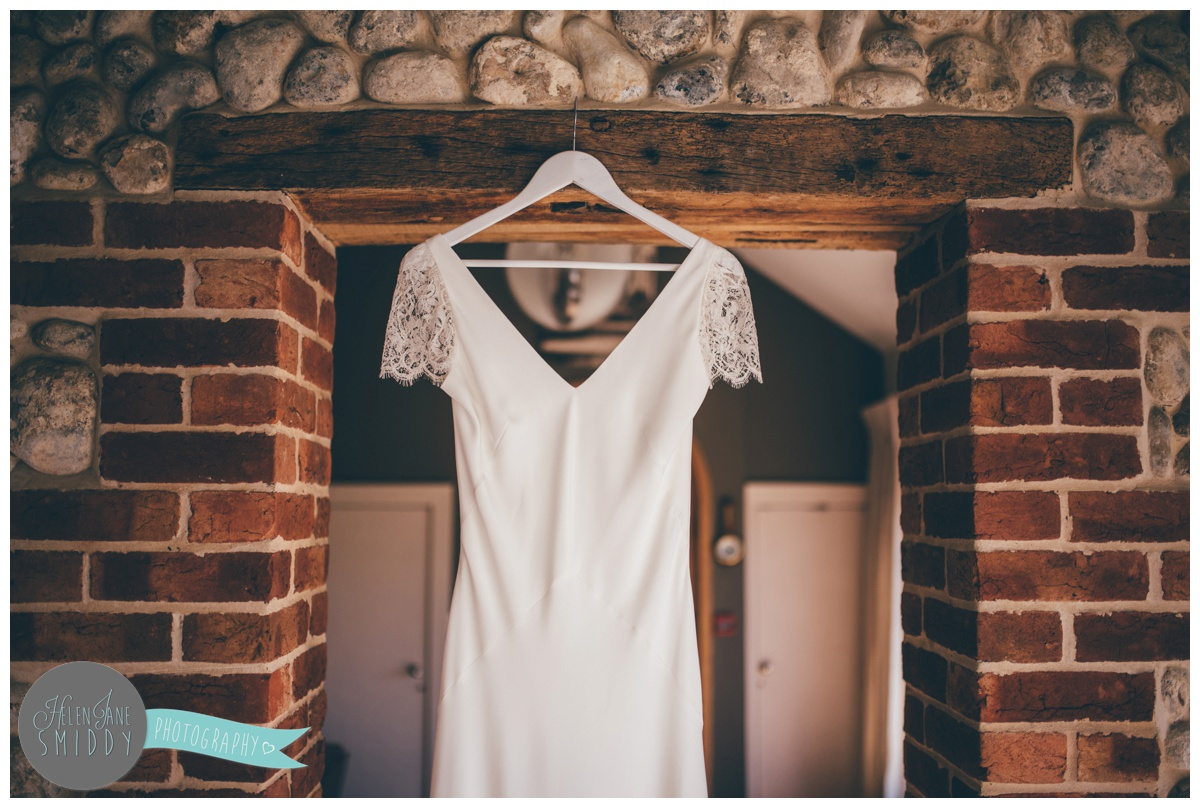 Sarah's beautiful slim-fitted wedding gown hung up at Barn Drift in Norfolk.