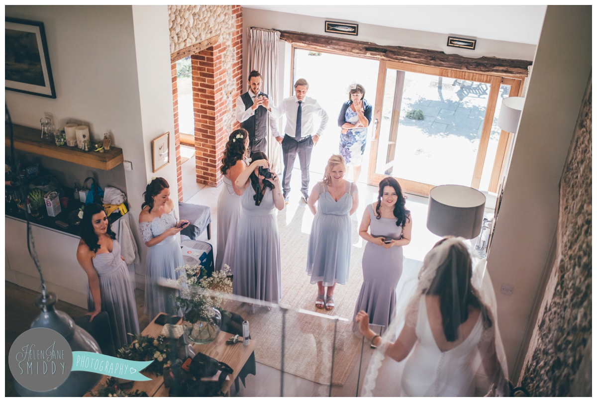 The bridal party look on as the bride arrives on the wedding morning.
