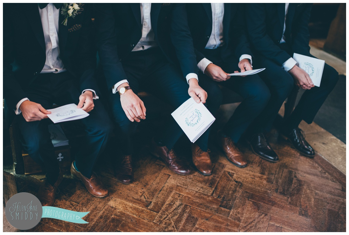 Groomsmen sit and wait for the bride at church.