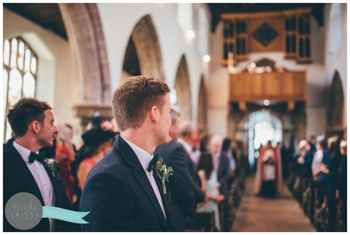 Groom, Joe, looks at his bride walking down the aisle.