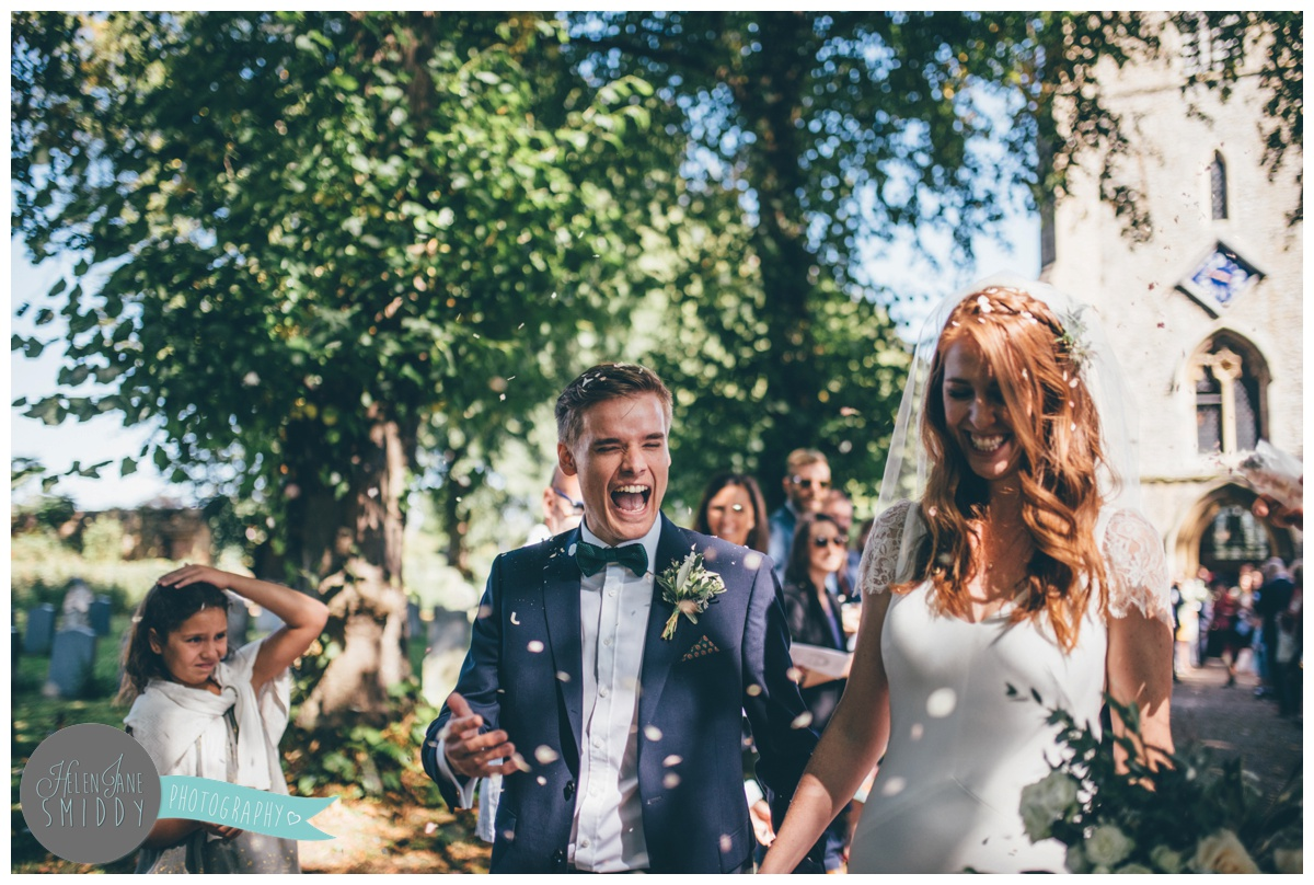 Colourful confetti gets thrown at the bride and groom at their sunny September wedding.