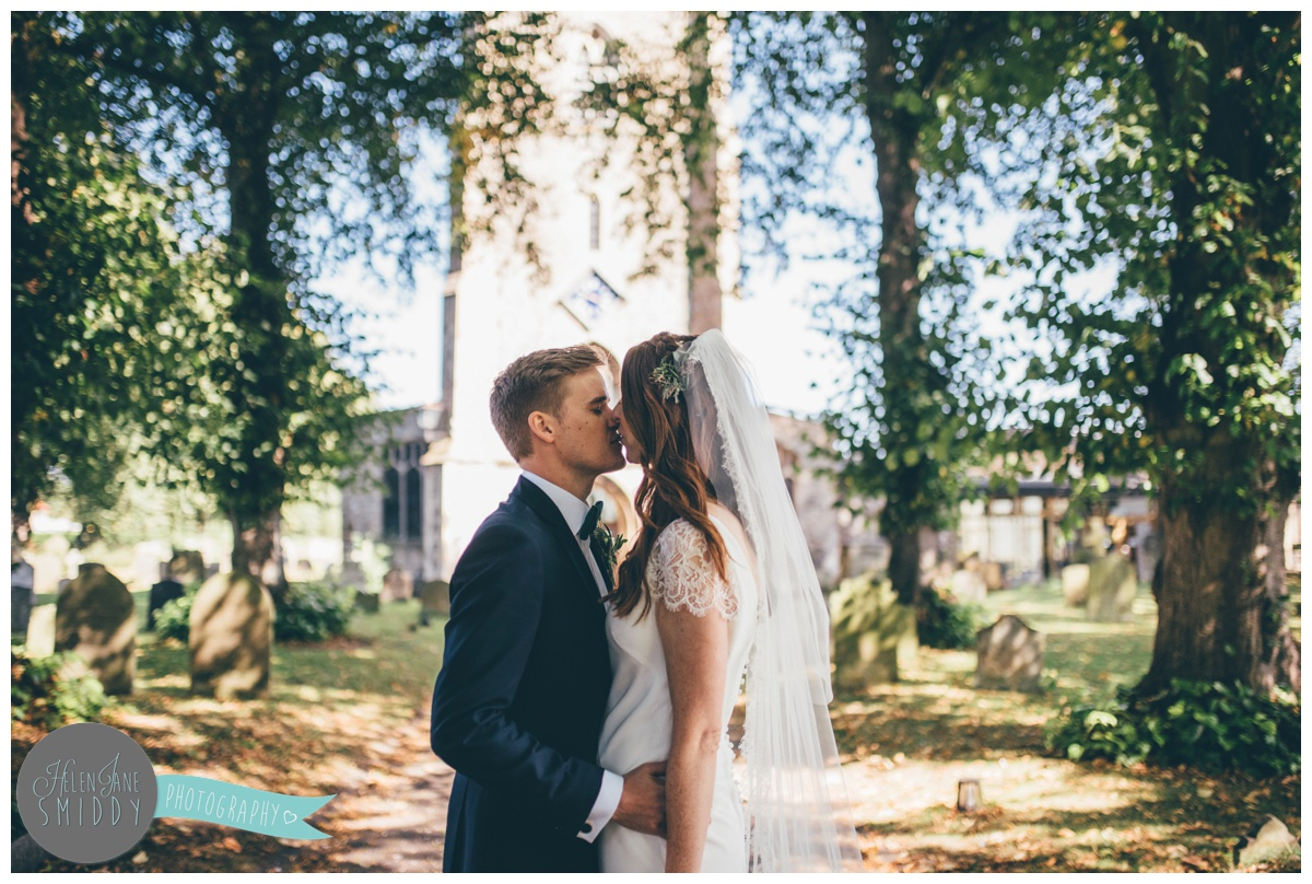 Bride and groom share a kiss after their ceremony outside church in Norfolk.