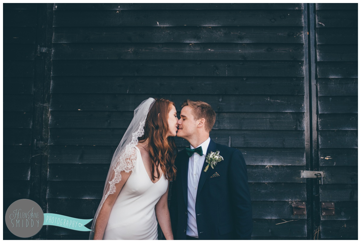 Bride and Groom kiss at their beautiful September wedding at Barn Drift in Norfolk.