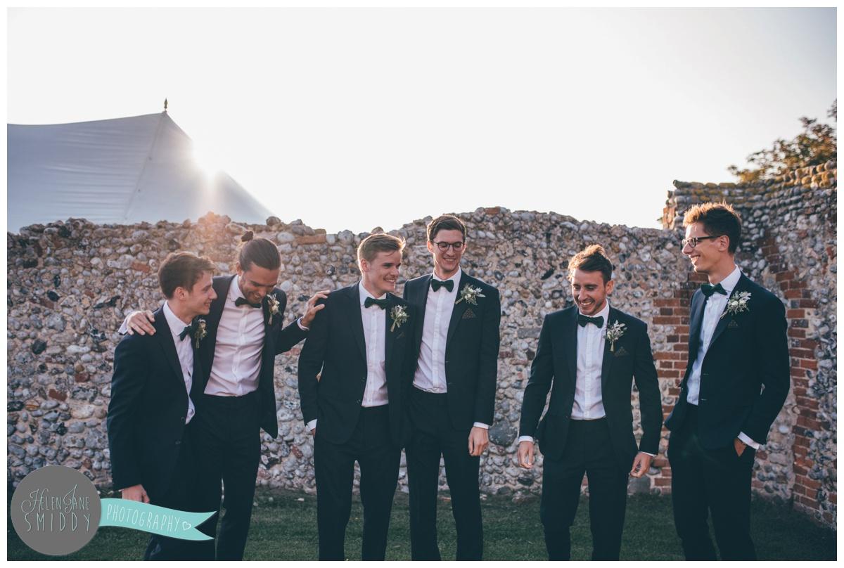 Groomsmen joke together at a Barn Drift wedding in Norfolk.