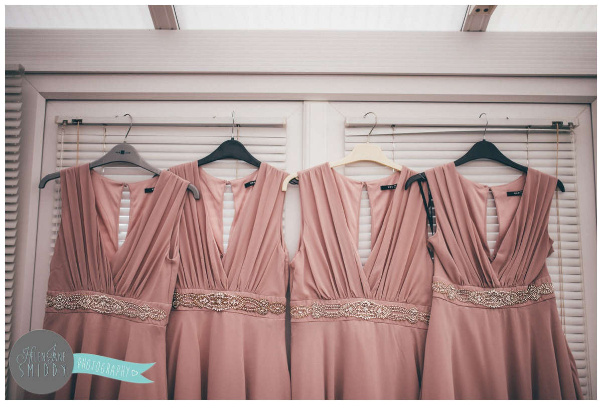 The blush pink bridesmaid dresses hung up on the morning of the wedding.