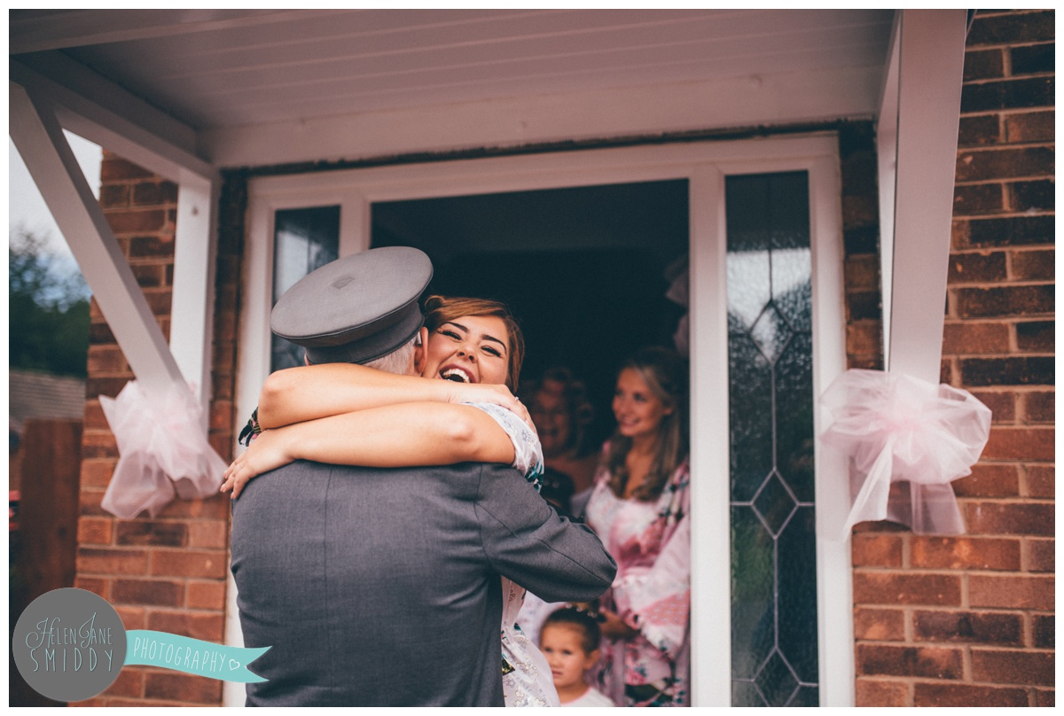 The beautiful bride hugs her chauffeur when he arrives on  the morning of her wedding.