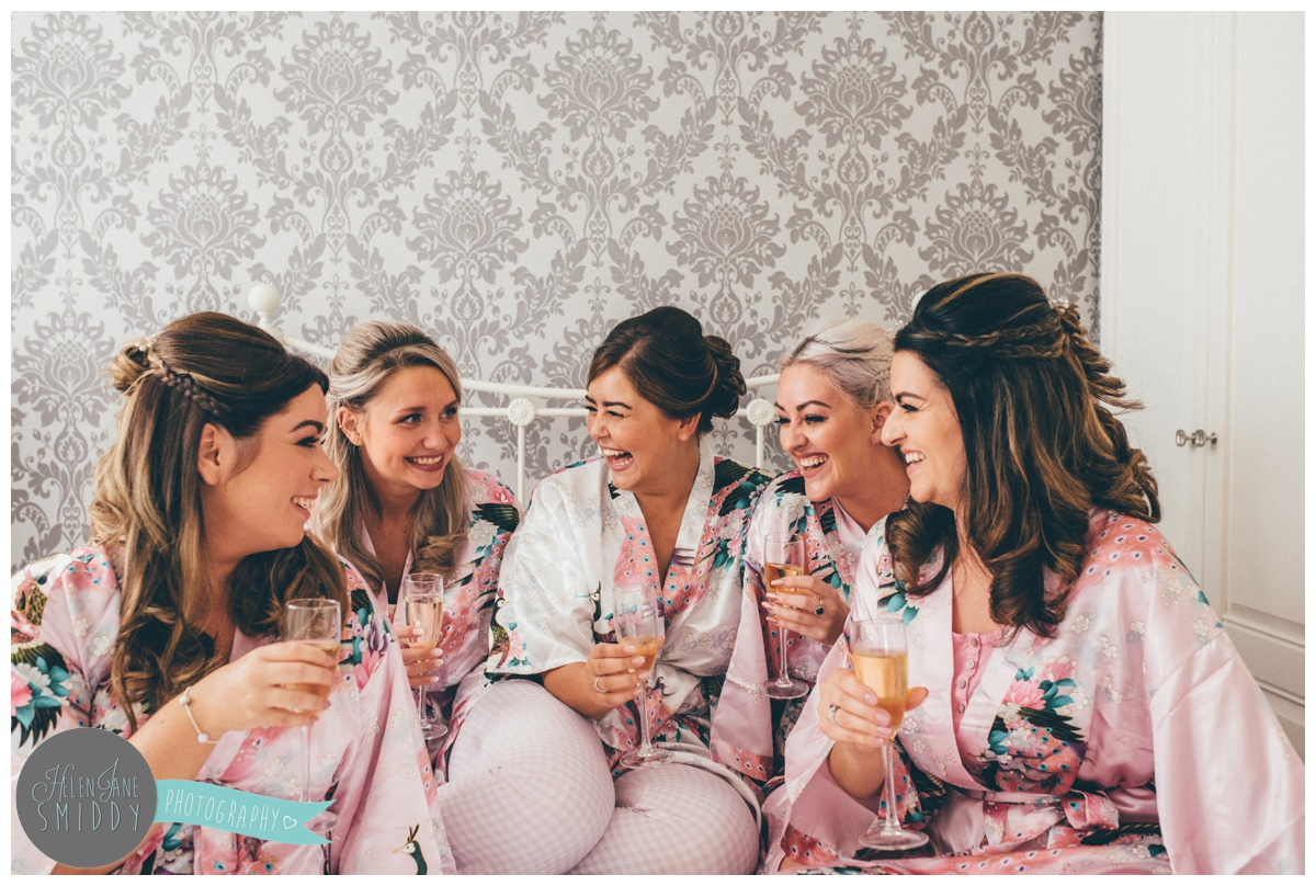 The bride sits with her bridesmaids laughing on the bed on the morning of her wedding.
