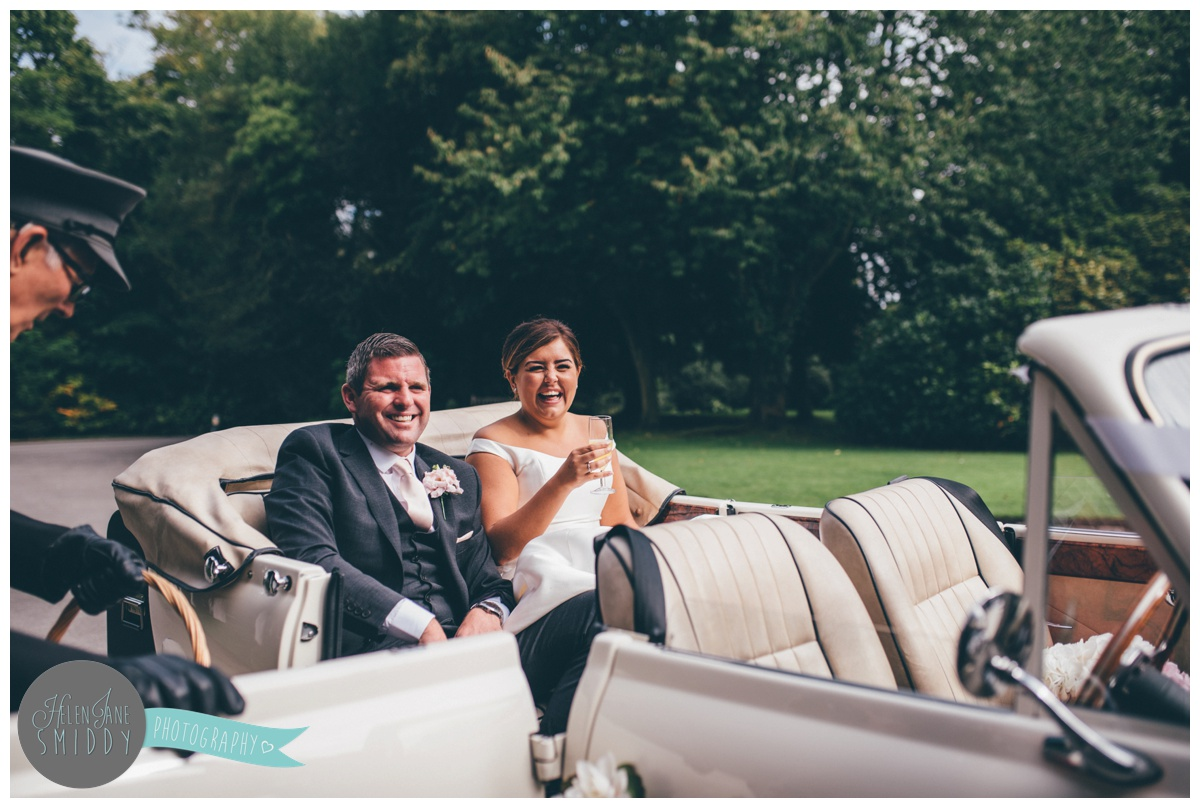 The bride and groom arriving at their wedding venue in their chauffeur driven car.