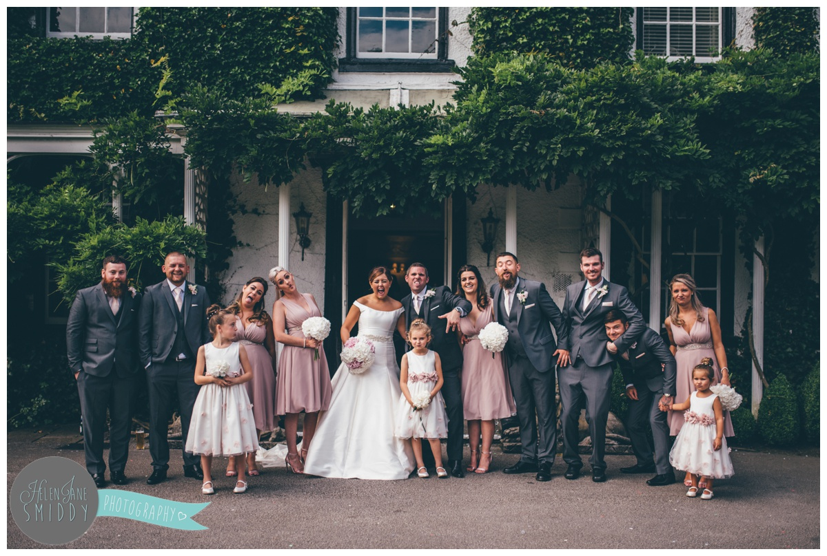 The ful wedding party outside the porch of Statham Lodge in Cheshire.