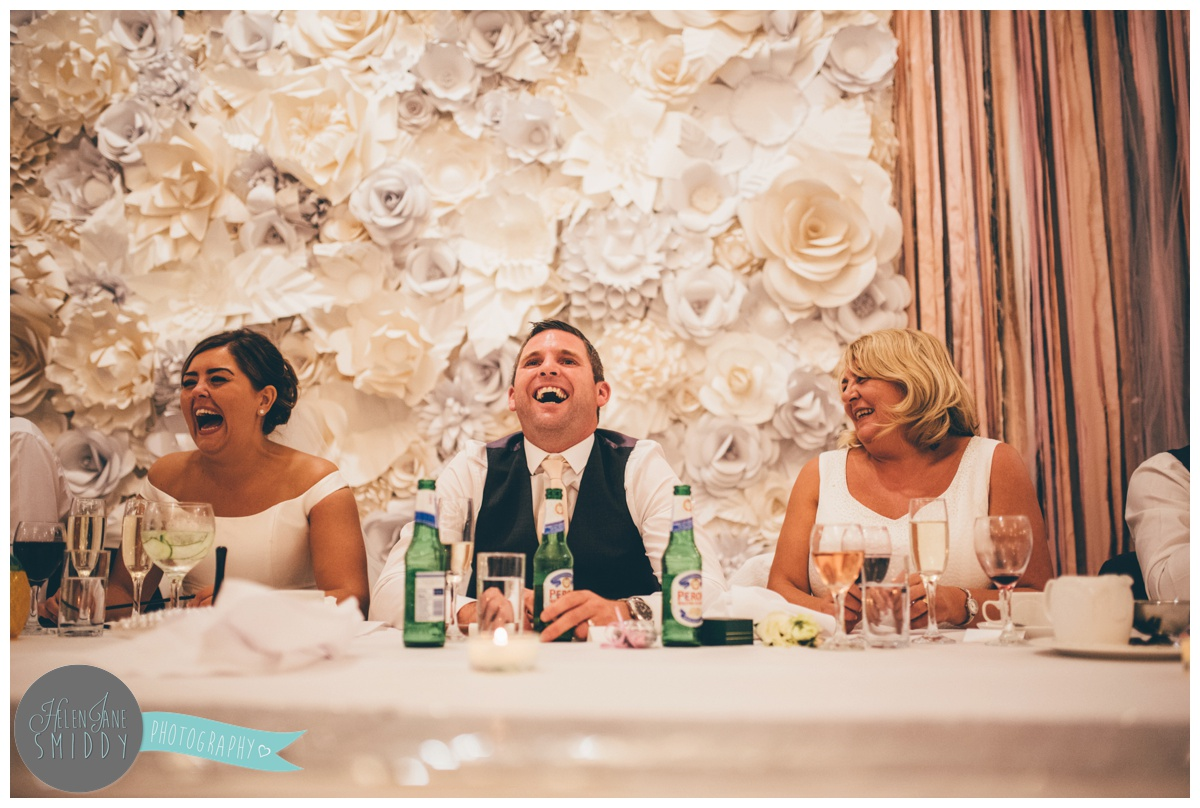 Groom laughs as his best man makes jokes during his speeches.
