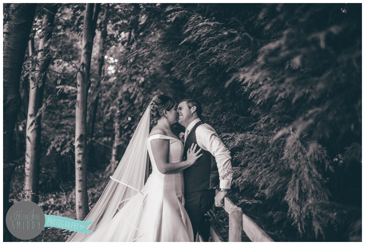 The new mr and mrs share a kiss in the woodland at Statham Lodge in Cheshire