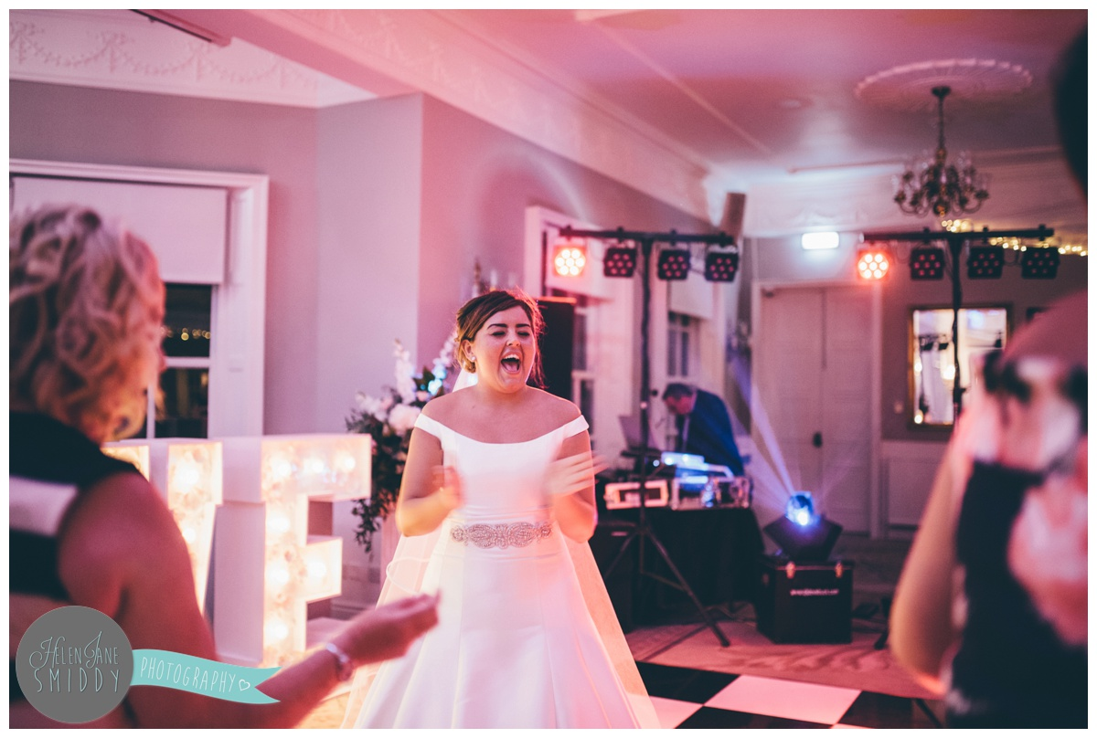 The beautiful bride sings along happily on the dancefloor at Statham Lodge in Cheshire.