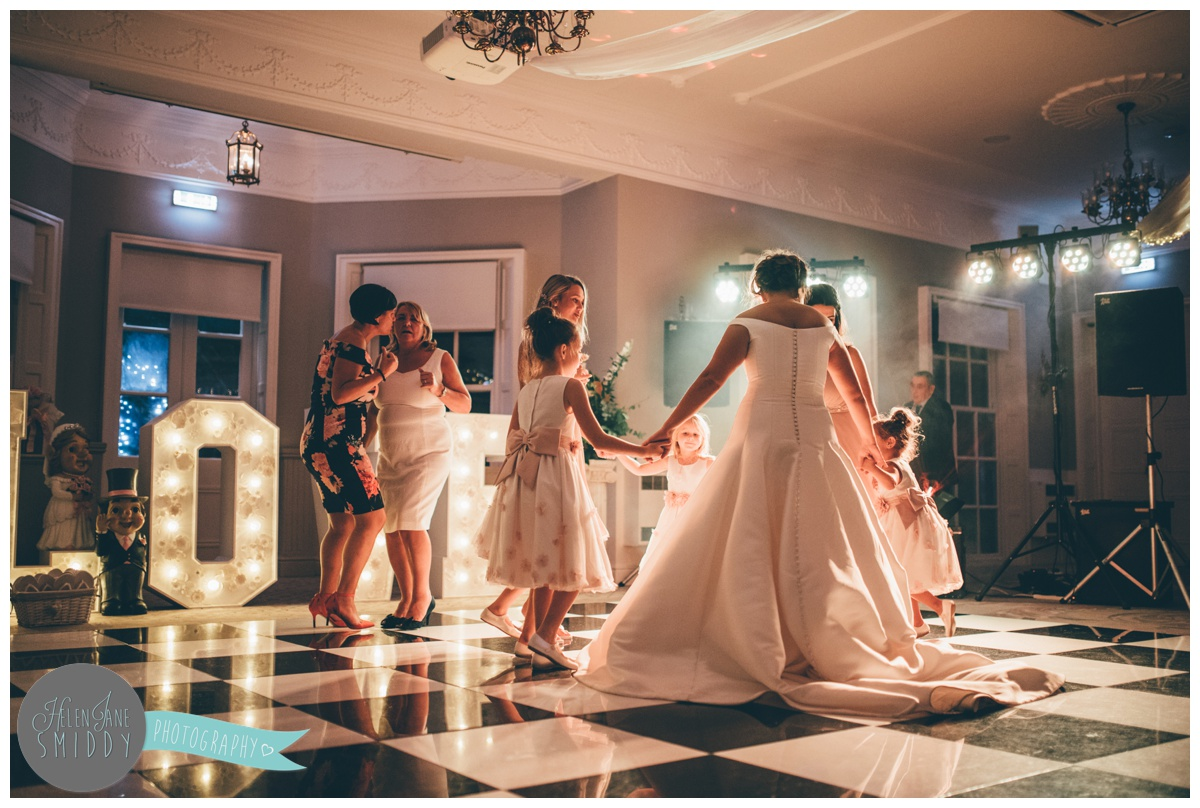 The bride dances on the beautifully lit dancefloor with her bridesmaids at Statham Lodge in Cheshire