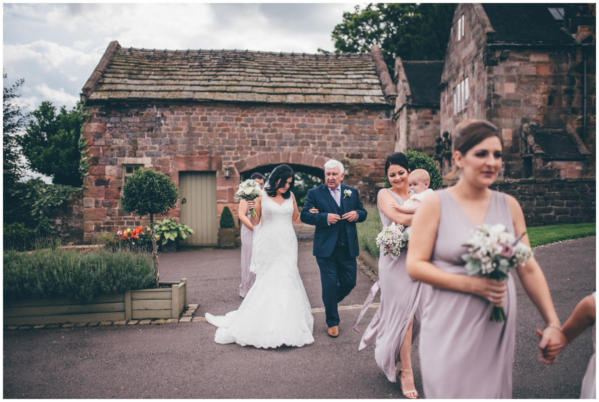 The bridesmaids lead the bride and her father into the ceremony room at The Ashes wedding barn in Staffordshire.