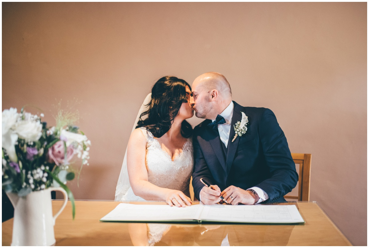 The newlyweds kiss after signing the register  at The Ashes wedding barn in Staffordshire.
