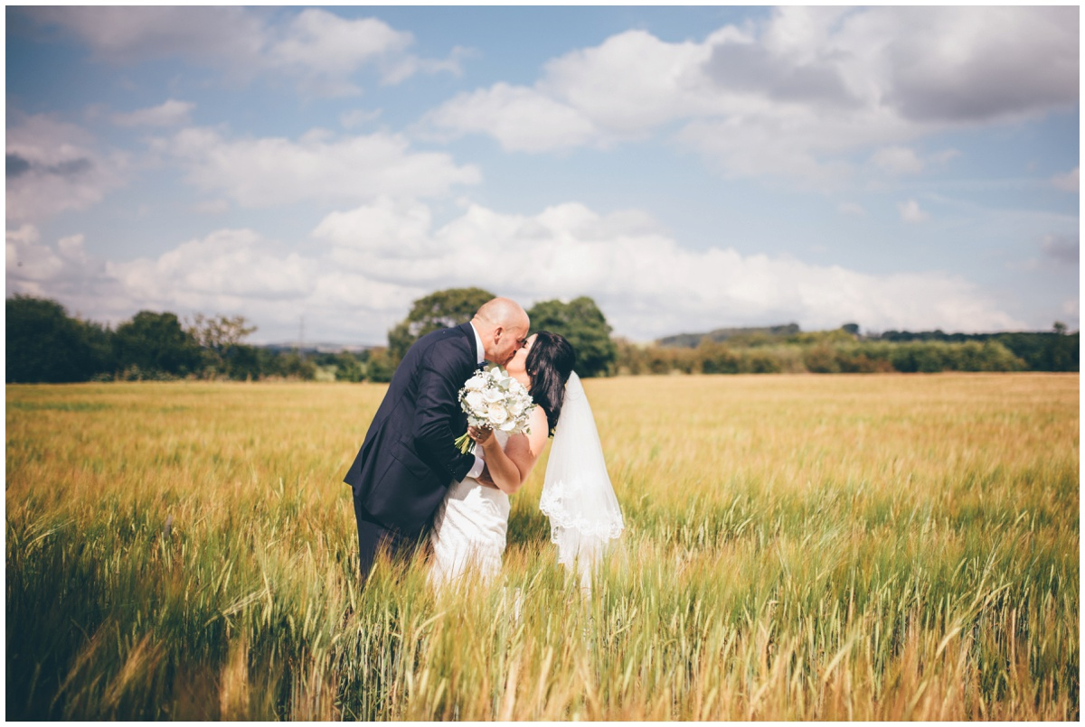 Amy and Phil share a kiss in a cornfield at The Ashes wedding barn in Staffordshire.