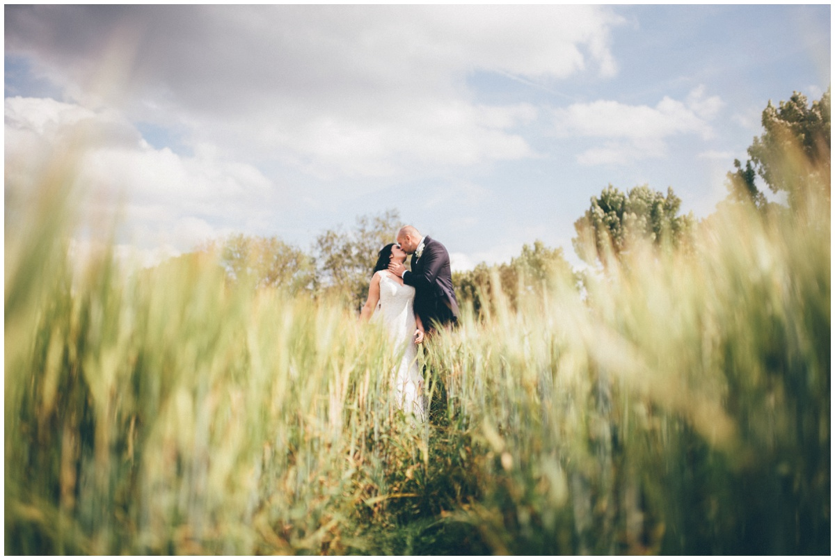 Beautiful symmetrical wedding photograph in a cornfield  at The Ashes wedding barn in Staffordshire.