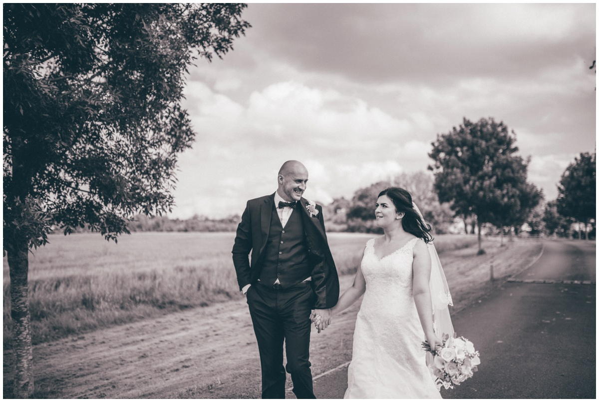 The bride and groom stroll, hand-in-hand towards their wedding venue, The Ashes wedding barn in Staffordshire.