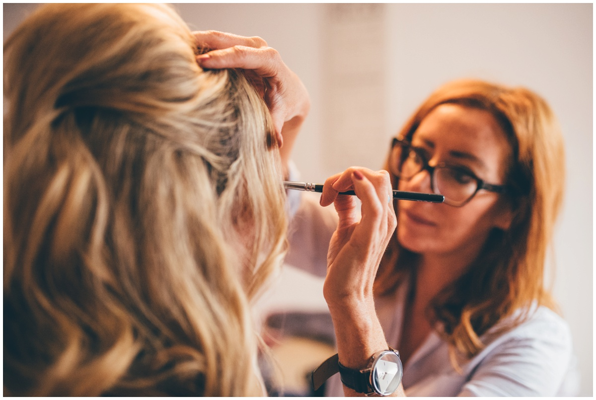 Professional make-up artist concentrates on the bride's eye make-up.