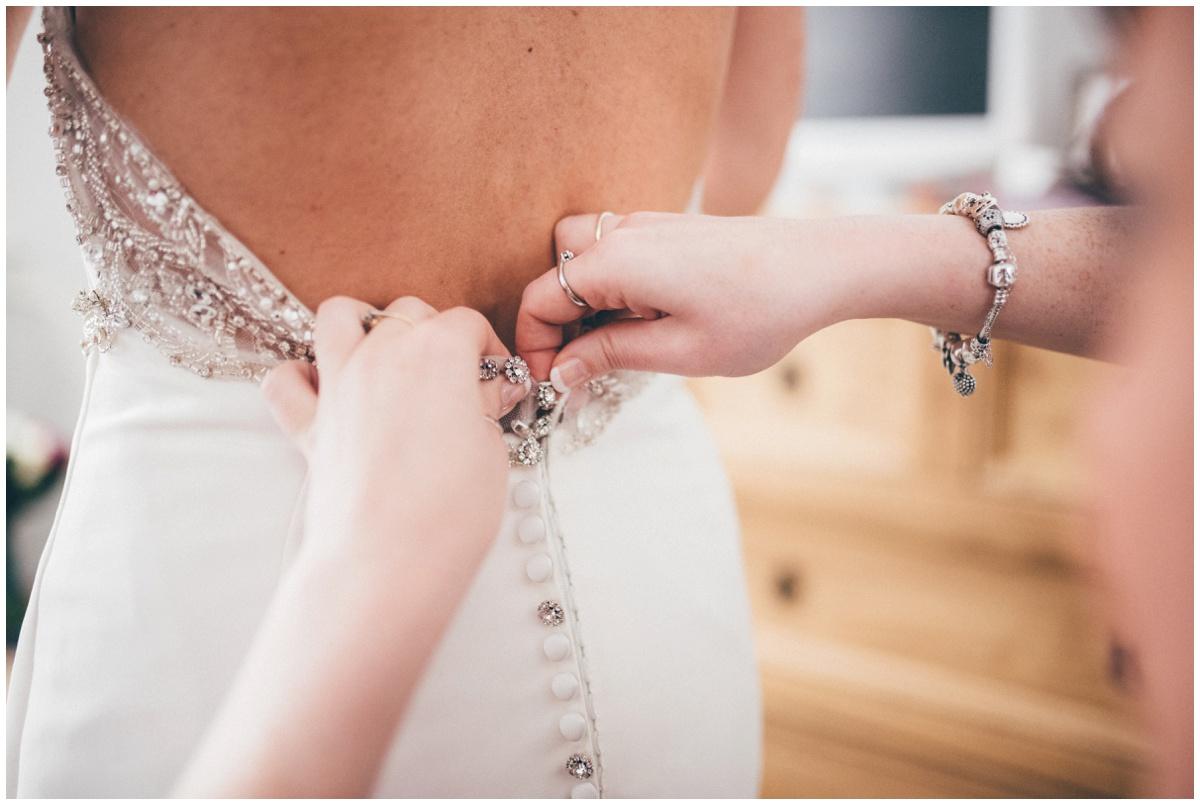 The bride's best friend fasten up her wedding dress.