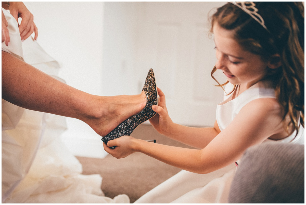 The flowergirl puts on the bride's beautiful Jimmy Choo shoes.