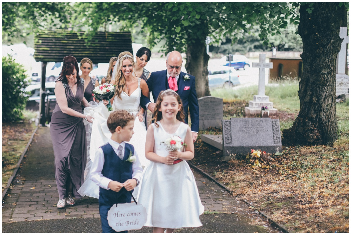 The bride and her dad lead the bridal party into St Mark's Church in Worsley for the wedding ceremony.