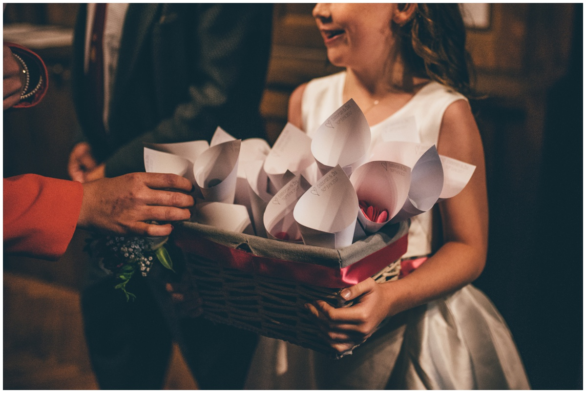 The flowergirl hands out confetti to the wedding guests at St Mark's Church in Worsley.