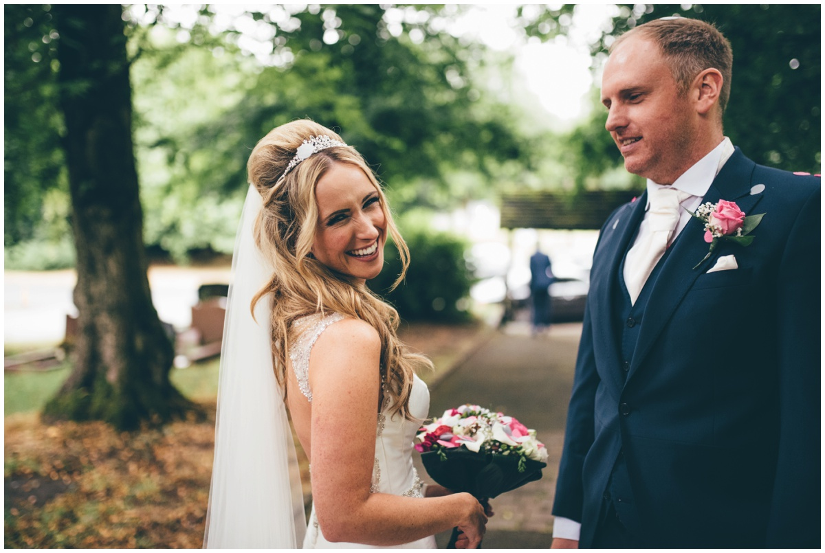 The beautiful bride beams at her Cheshire wedding photographer outsider her Worsley church.