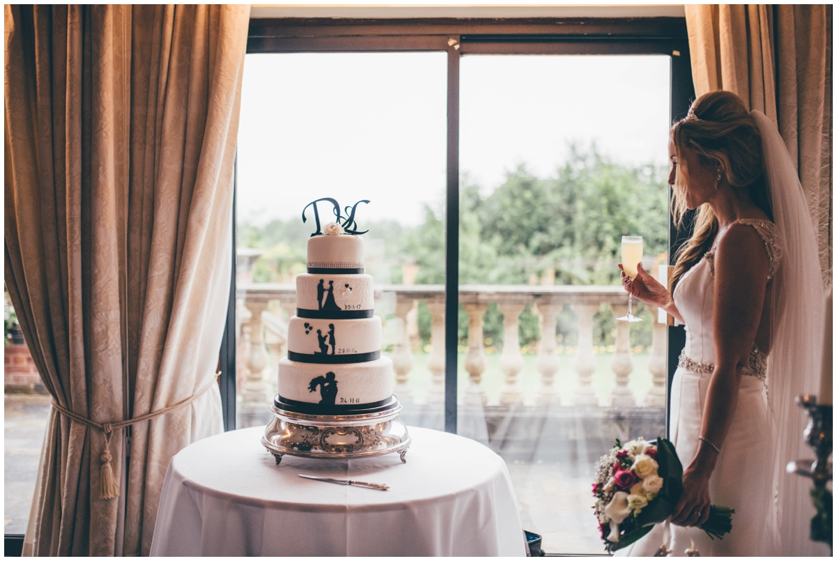 The beautiful bride admires her silhouette themed wedding cake.