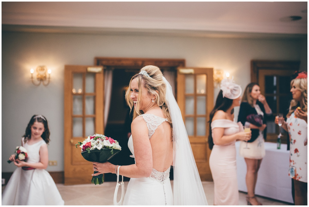 The beautiful bride greets her wedding guests at her reception at Willington Hall in Cheshire.