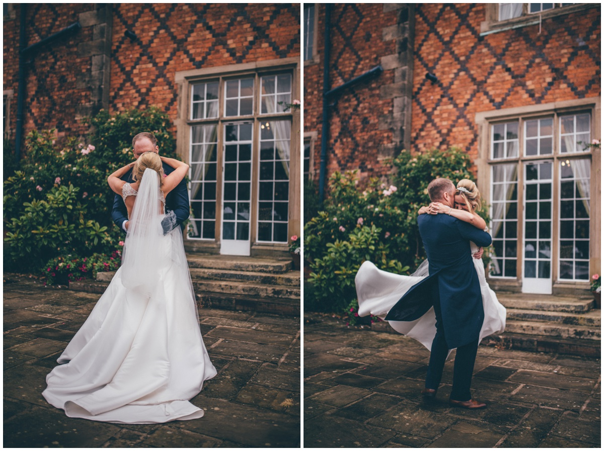 Groom swinging his laughing bride around, her gorgeous long train floats in the wind.