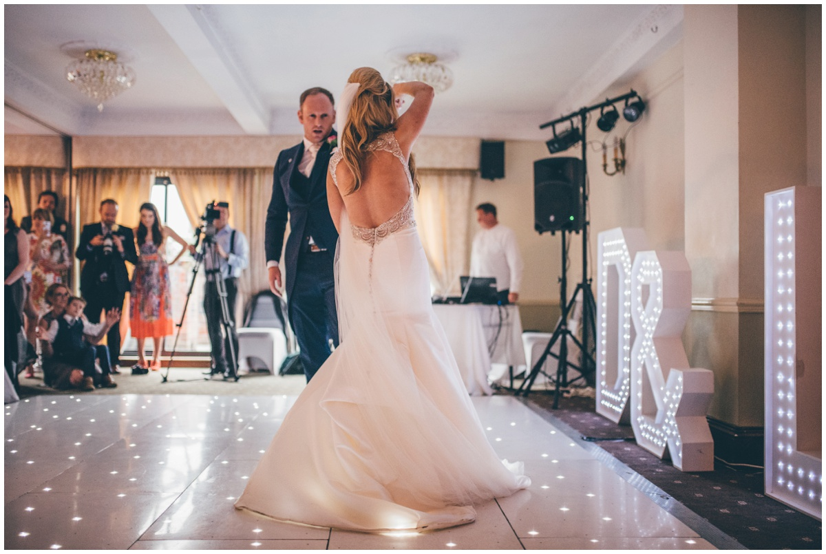The groom twirls his new wife around on the dancefloor during their First Dance.