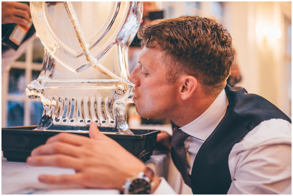 A wedding guest tries the jagermeister with the luge at the fun wedding reception at Willington Hall.