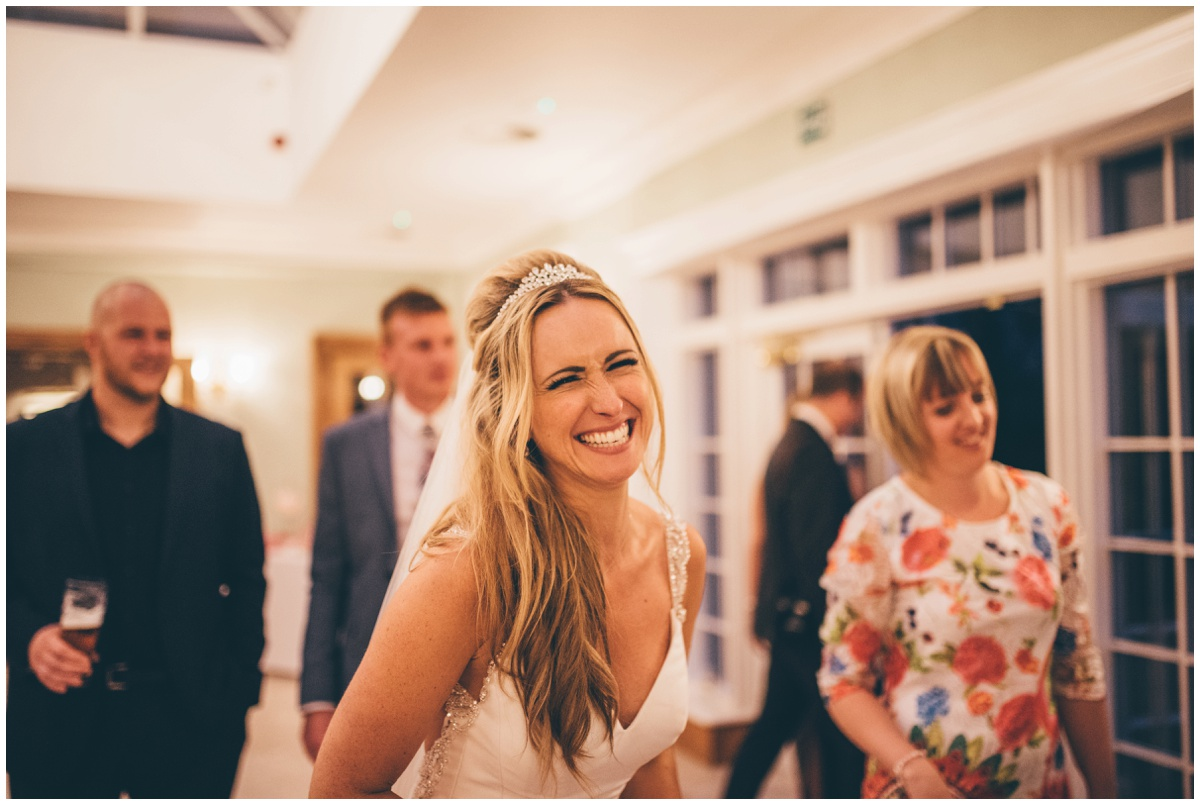 The new bride grins at her Frodsham wedding photographer at her wedding at Willington Hall in Cheshire.