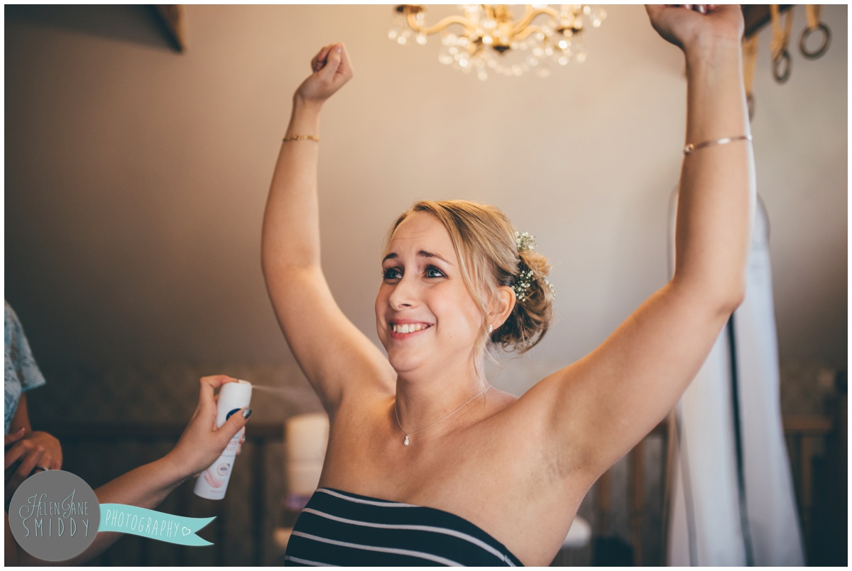 Funny bride has deodorant sprayed on her wedding morning.