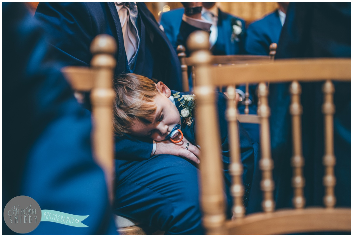 Cute little pageboy falls asleep during the wedding ceremony.