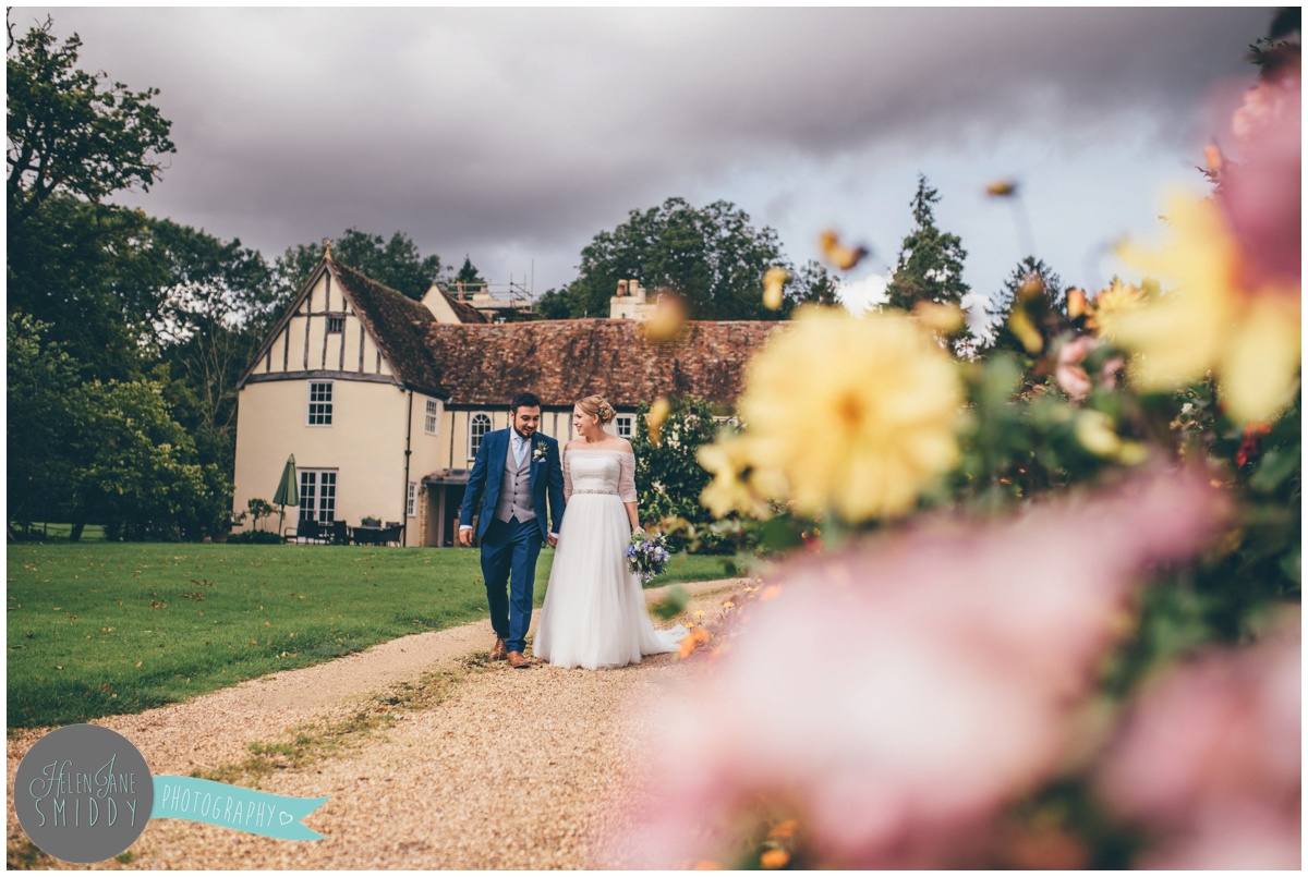 The bride and groom stroll through the pretty and flowery gardens at Bassmead Manor in Cambridgeshire.