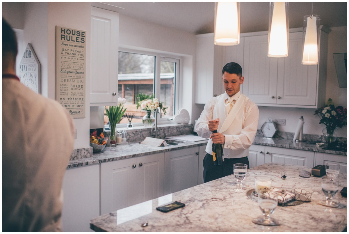 The groom opens a bottle of champagne for himself and his groomsmen.