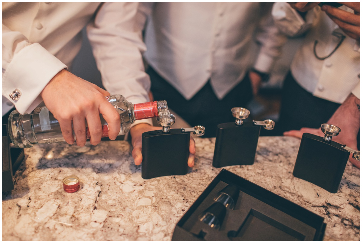 The groom pours vodka into hip flasks for himself and the boys.
