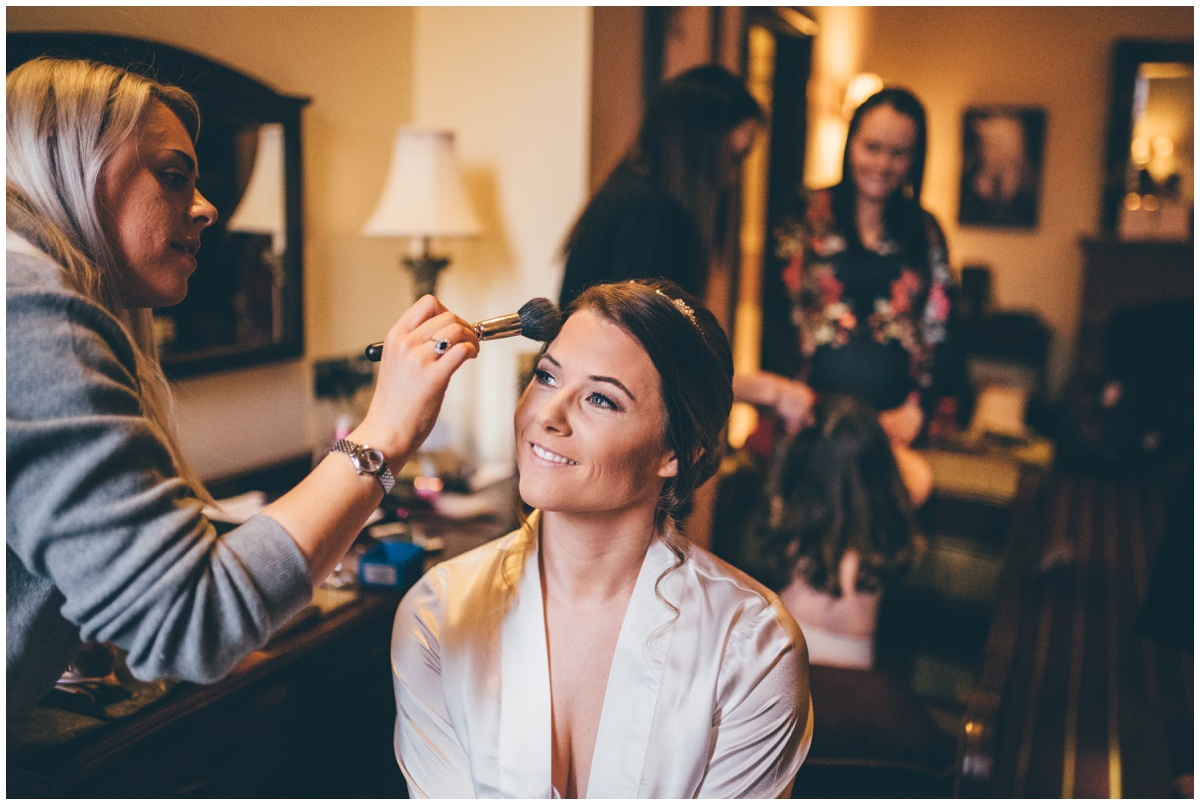 Beautiful bride has finishing touches to her wedding make up.