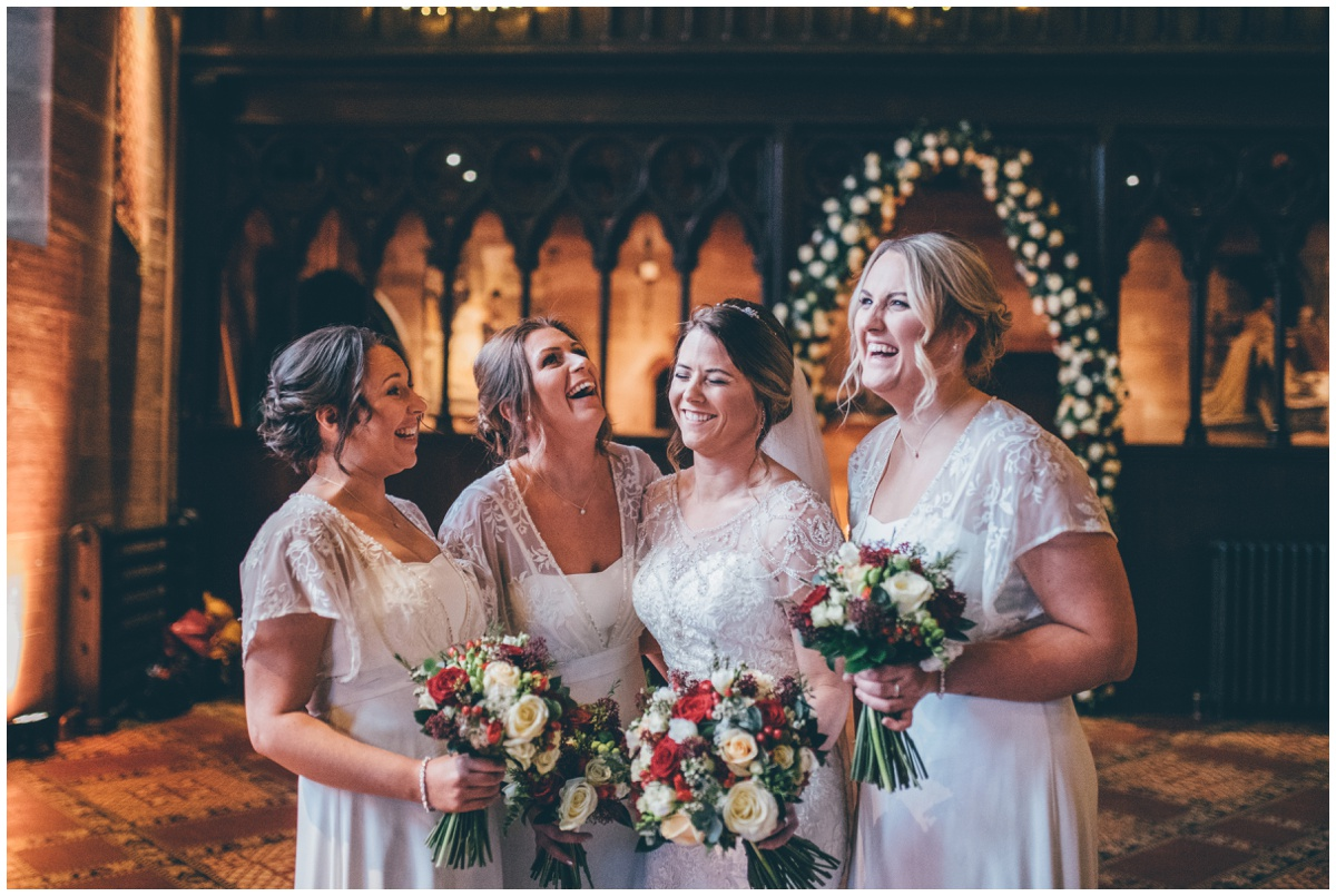 The bride laughs with her bridesmaids at Peckforton Castle.